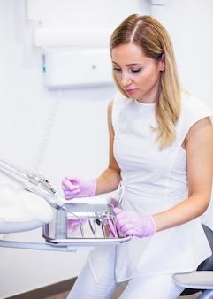 Weiblicher zahnarzt, der zahnmedizinische instrumente auf behälter betrachtet
