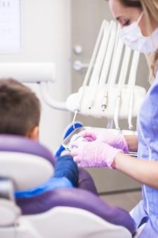 Weiblicher zahnarzt, der zahnputzform in der klinik betrachtet