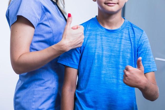 Weiblicher zahnarzt mit dem patienten daumen oben gestikulierend