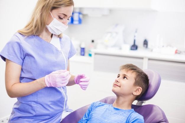 Weiblicher zahnarzt mit der chirurgischen maske, die naher patienten des scalers in der klinik hält