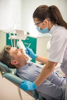 Weiblicher zahnarzt mit seinem älteren kunden einen patienten überprüfend.