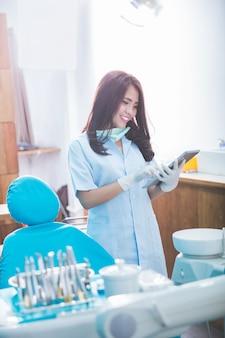 Weiblicher zahnarzt mit tablette über medizinischer büroklinik