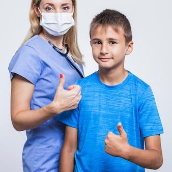 Weiblicher zahnarzt und junge, die oben daumen gestikuliert