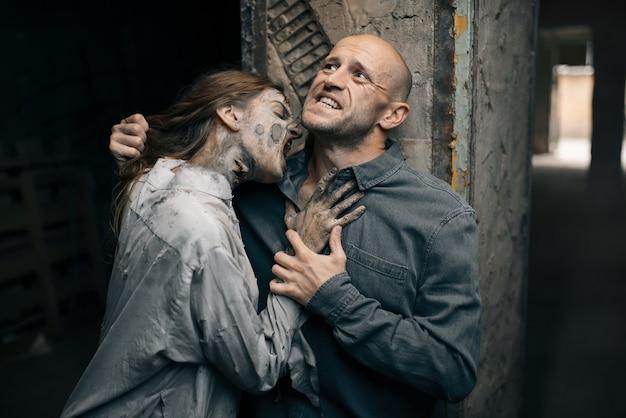 Weiblicher zombie beißt einen mann in den hals, todesfalle
