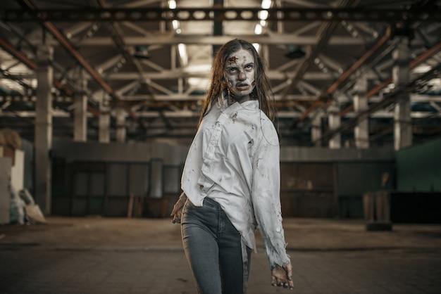 Weiblicher zombie, der in verlassener fabrik, unheimlicher ort geht. horror in der stadt, gruselige krabbeltiere, weltuntergangsapokalypse, blutige böse monster