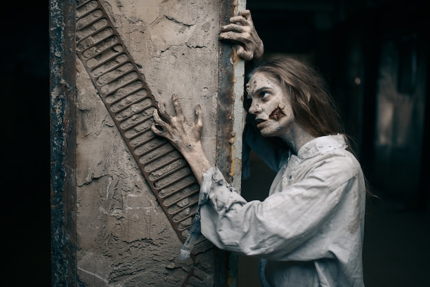 Weiblicher zombie in verlassener fabrik, teufel