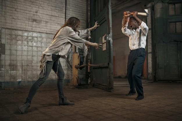 Weiblicher zombie kämpft mit erschrockenem mann in verlassener fabrik. horror in der stadt, gruselige krabbeltiere, weltuntergangsapokalypse, verdammt böse monster