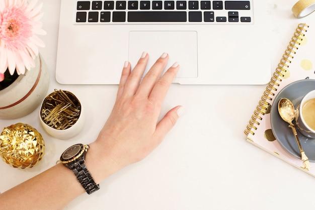 Weibliches arbeitsplatzkonzept in der flachen lageart mit laptop, kaffee, blumen, goldener ananas, notizbuch und büroklammern, frauenhand. blogger arbeiten. draufsicht, hell, rosa und gold