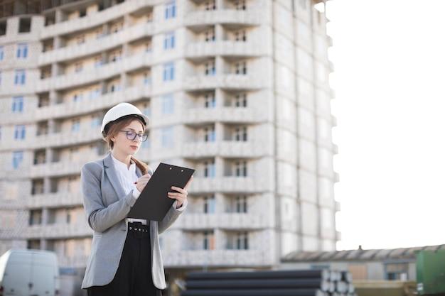 Weibliches architektenschreiben auf klemmbrett am standort