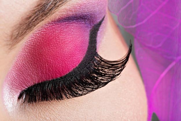 Weibliches auge der nahaufnahme mit hellem rosa make-up der schönen mode