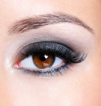 Weibliches auge mit dunkelbraunem glamour-make-up - makroaufnahme