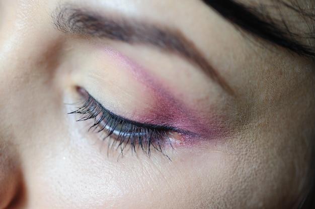 Weibliches auge mit einer hellen make-upnahaufnahme