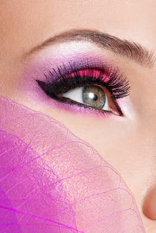 Weibliches auge mit hellem rosa make-up der schönen mode