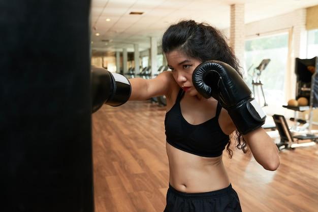Weibliches boxertraining in der turnhalle in den boxhandschuhen