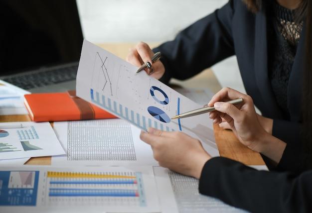 Weibliches buchhalterteam analysiert datendokumente im büro.