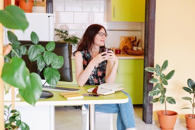 Weibliches büro des modells at home using her computer und trinkender kaffee