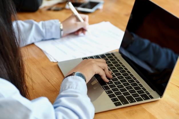 Weibliches büropersonal macht sich notizen und benutzt laptop.