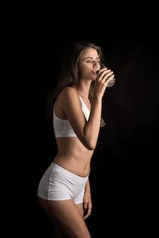 Weibliches eignungsmodell, das ein wasserglas hält
