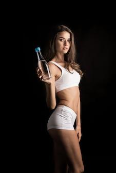 Weibliches eignungsmodell, das eine wasserflasche hält