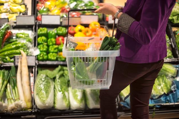 Weibliches einkaufen der ernte im gemischtwarenladen