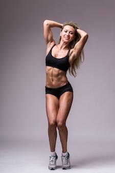 Weibliches fitnessmodell in der sportbekleidung auf grauem hintergrund