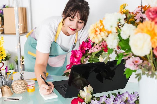 Weibliches floristenschreiben auf notizblock mit laptop über schreibtisch