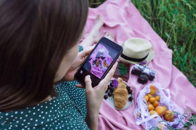 Weibliches fotografieren des picknicks auf grünem gras im freien
