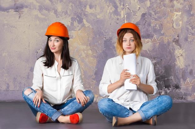 Weibliches frauenmädchen von zwei glücklichen lustigen netten architekten in den orange bauschutzgebäudesturzhelmen, die auf boden mit architekturzeichnungen und -entwürfen sitzen.