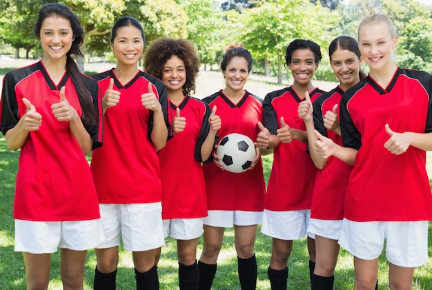 Weibliches fußballteam, das oben daumen am park gestikuliert