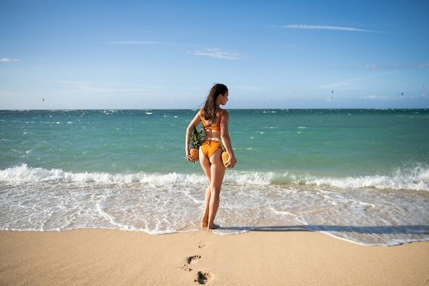 Weibliches gesäß im badeanzug, sexy arsch. frau, die eine ananas auf dem tropischen hintergrund des dominikanischen oder hawaii-strandes mit exemplar hält.