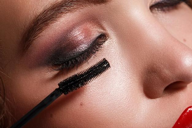 Weibliches gesicht und mascara-pinsel