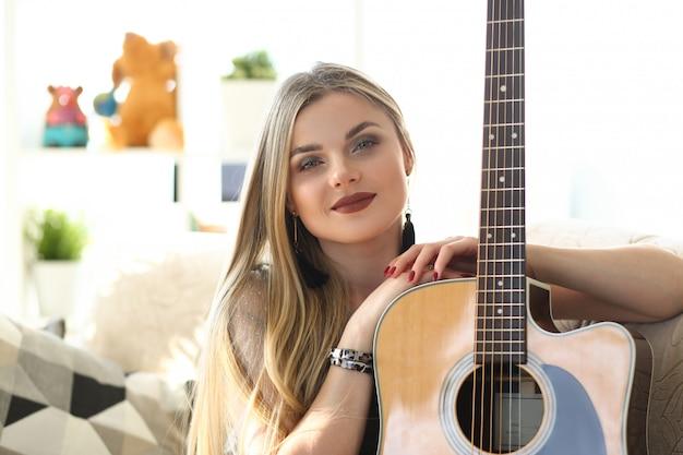 Weibliches gitarrist-musikalisches ausführend-porträt. attraktive kaukasische frau, die instrument hält. junger komponist sit on couch kopf und schultern front shot. schönes musiker-mädchen, das kamera betrachtet