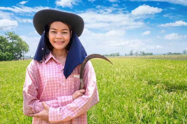 Weibliches glückliches lächeln des asiatischen jungen landwirts und halten der sichel auf einem grünen reisgebiet und einem blauen himmel
