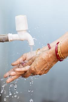 Weibliches händewaschen unter dem wasserhahn - bedeutung des händewaschens während der covid-19-pandemie