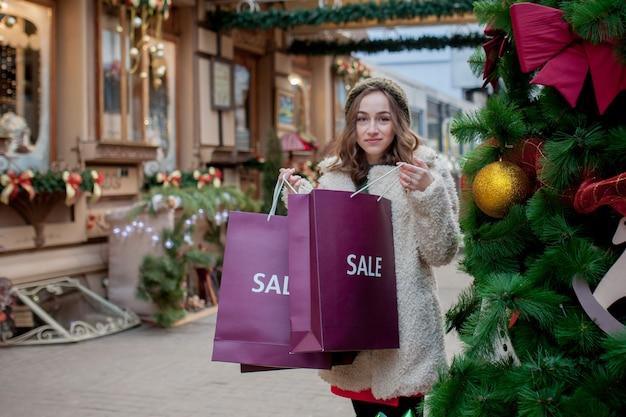 Weibliches halten des weihnachtseinkaufstaschengeschenks
