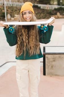 Weibliches haltenes skateboard der vorderansicht