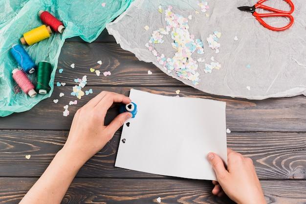 Weibliches handausschnittpapier mit herzform-lochermaschine nahe threadspulen und -schere über tabelle