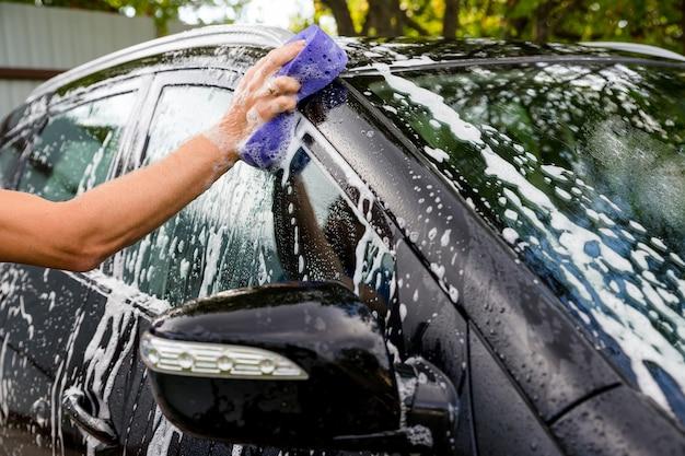 Weibliches handwaschautomobil an der manuellen autowaschselbstbedienungsstation