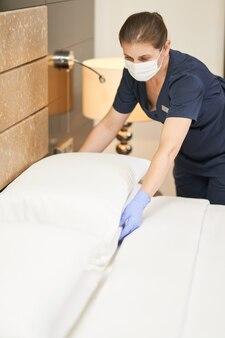 Weibliches hausmädchen in schutzmaske, das weißes kissen auf dem bett im modernen hotelzimmer auflockert. hotelservicekonzept