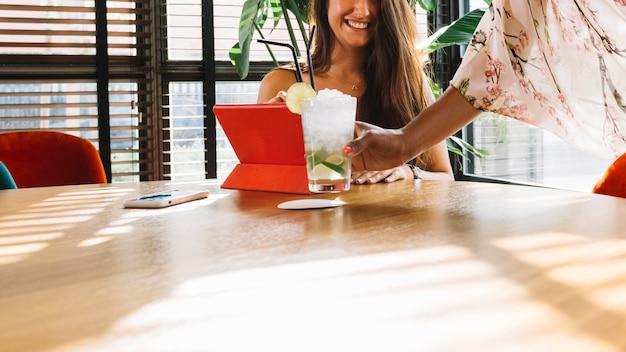 Weibliches kellnerinumhüllungscocktail zum weiblichen kunden auf holztisch