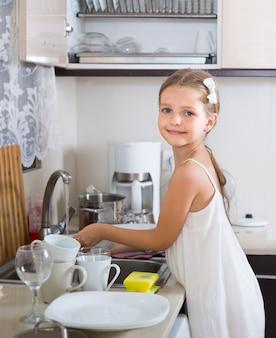 Weibliches kind, das dishware zu hause säubert