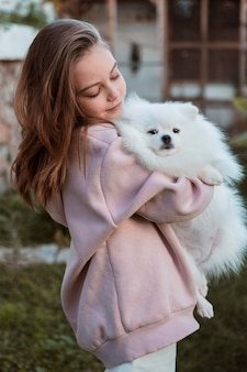 Weibliches kind, das ihren flauschigen hund umarmt
