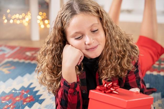 Weibliches kind, das von weihnachten mit einem geschenk träumt