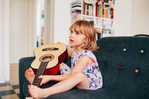 Weibliches kind drinnen zu hause, das gitarre hält