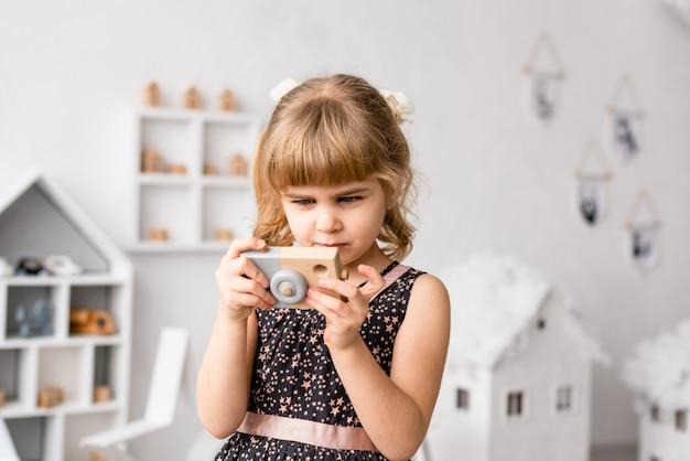 Weibliches kleinkind halten hölzerne fotokamera am weißen hintergrund
