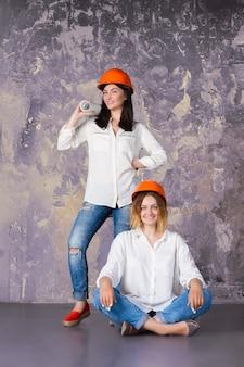 Weibliches mädchen der lustigen netten architekturfrau zwei in den orange hochbausturzhelmen mit dem entwurf der konstruktionszeichnungen bereit zum neuen arbeitsdesigninnenraum