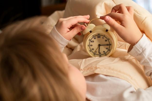 Weibliches mädchen des mädchens, das einen wecker in ihren händen nahaufnahme im bett am frühen morgen hält