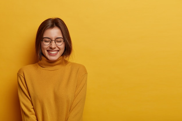 Weibliches mädchen mit zahnigem lächeln, blinzelt gesicht und fühlt sich froh, drückt positive gefühle aus, trägt lässigen langarmpullover, isoliert auf gelbem raum