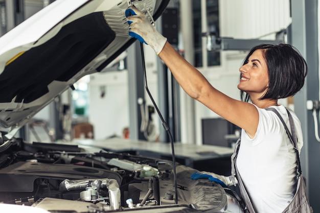 Weibliches mechanikerfestlegungsauto der seitenansicht
