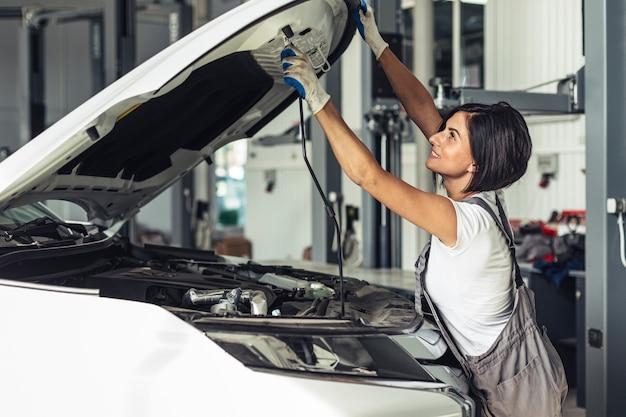 Weibliches mechanikerfestlegungsauto der vorderansicht